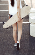 Rear view of skater girl walking away holding her longboard behind her back