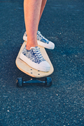 Girl standing on longboard with bruise on her lower leg, copyspace