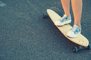 Young Girl legs standing on longboard closeup and a lot of copyspace