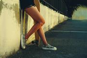 Girl with skateboard leaning back concete wall. Elegant slim legs of female longboard skater in skate park.