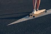 Skateboard on painted on asphalt arrow, legs on the board