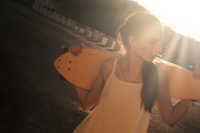 Young Woman with longboard behind her neck backlit by bright summer sun a lot of space for text