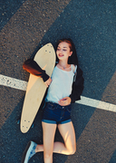 Skater girl lying down on asphalt surface of the road and enjoing summer warm weather after phisical activity, copyspace