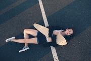Very tyred skater girl sleeping on asphalt in warm summer day, copyspace
