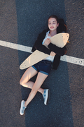Skateg girl lying down with her longboard on asphalt street surface above view