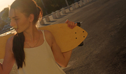 Girl with skatedoard behind her shoulders in summer looking away, shot with copyspace