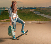 Hipster girl on skateboard with backpack in her hands