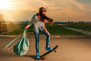 Hipster female on skateboard with backpack in her hands backlit in warm sunset light making trick on the road