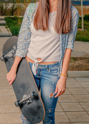 Hipster girl in jeans and boho jacket holding skateboard front view