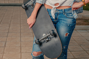 Girl holding skateboard in front of her body shot with copyspace