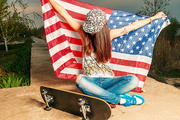Patriotic girl celebrating legalize with US flag in her hands sitting on lane with her skateboard near