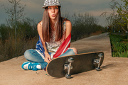 Skater girl sitting on cement lane with her skateboard draped in US flag instagram color toned