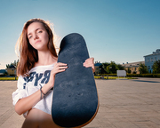 Wide angle shot of skater girl with skateboard on her shouler, a lot of space for text on the sky