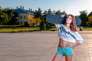 Sporty girl in short shirt showing her bare belly posing with skateboard on her shoulder, looking at camera with blank expression, a lot of space for text.