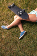 Young female skater with Bare legs sitting on grass faceless closeup