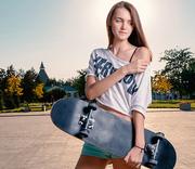 Long haired girl holding skateboard posing with bare shoulder