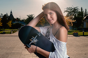 Smiling girl with skateboard in summer city backlit.