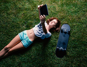 Happy girl lying down the park grass and make selfie with her skateboard lying near top view.