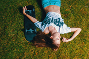 Teen Girl skater resting on grass with her skateboard near top view