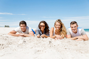 Company of young friends on the beach relaxing on white sand