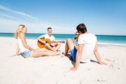 Beautiful young people with guitar having fun on beach