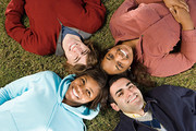 Four students lying down outdoors