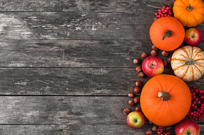 Autumn harvest still life with pumpkins, wheat ears, hazelnuts, garlic, onion and rosehip berries on wooden background