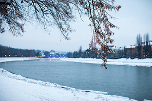 Snow-covered embankment in evening city. Beautiful winter landscape
