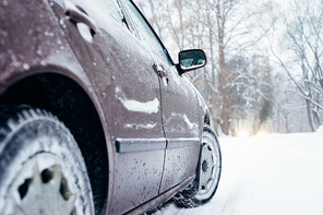 Car on winter road covered with snow. From ground view, selective focus