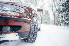 Car on forest road covered with snow. From ground view, selective focus on winter tires