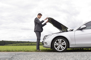 Full length side view of young businessman opening broken down car hood at countryside