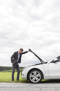 Side view of young businessman examining broken down car engine at countryside