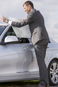 Full length side view of young businessman reading map by car at countryside