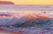 Amazing hawaiian beach. Wave in ocean at sunset or sunrise with surfer. Wave with warm sunset colors. Oahu beach, USA.