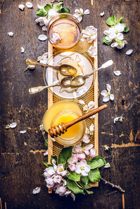 Honey, tea and spring blossom on honeycomb, dark wooden background, top view