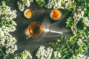 Cup of tea with acacia honey , blossom branches on rustic wooden background, top view. Healthy seasonal herbal tea