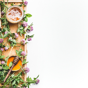 Honey in jar with dipper, honeycomb frame and wild flowers on white background, top view. Healthy  food, flat lay, border, vertical