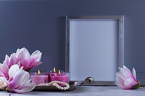 Gray room interior decor with magnolia flowers, burning hand-made candle and poster mock up