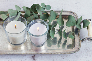 Natural eco home decor with green leaves and burning candles on table