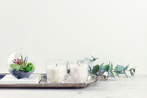 White room interior decor with burning candle and greenery