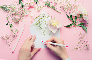 Female hands write with pencil on opened envelop with flowers arrangement . Florist  decoration equipment on pink table background, top view. Invitation , greeting and holiday, concept