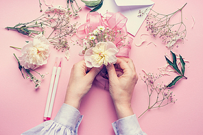 Female hands making lovely floral arrangement with flowers and ribbon on pale pink background, top view. Creative greeting, Invitation and holiday concept