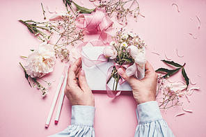 Female hands making lovely floral arrangement with flowers and envelop on pale pink background, top view. Creative greeting, Invitation and holiday concept