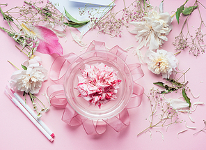 Creative Pink Florist workspace. Pretty floral decoration arrangement with pink roses and plant leaves in glass vase with water and florist decoration equipment, top view. Holiday concept