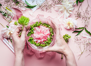 Creative Florist workspace. Female hands making pretty floral decoration arrangement with pink roses and green plant leaves in glass vase with water and florist decoration equipment, top view