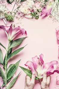 Florist workspace. Female hands holding beautiful pink lily flowers on pastel table with  florist decoration equipment, top view, frame. Creative Flowers arrangement. Invitation and holiday, concept