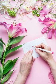 Female hands write with pencil greeting card on Blank envelop on pink table background with lily flowers and florist decoration equipment, top view. Creative  Invitation and holiday  concept
