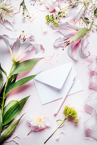 Blank white envelop with pencil and various decoration equipment and flowers on pink pale table background, top view. Festive Invitation , Creative  greeting and holiday, concept