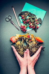 Female hands holding a Creative autumn flowers bouquet on florist workspace table background with opened envelop , shears , pencil, top view.  Invitation , greeting and holiday, concept