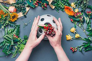 Female hands make Creative autumn floral arrangement with various flowers and plant leaves arrangement on blue table , top view. Florist workplace. Greeting and holiday, concept